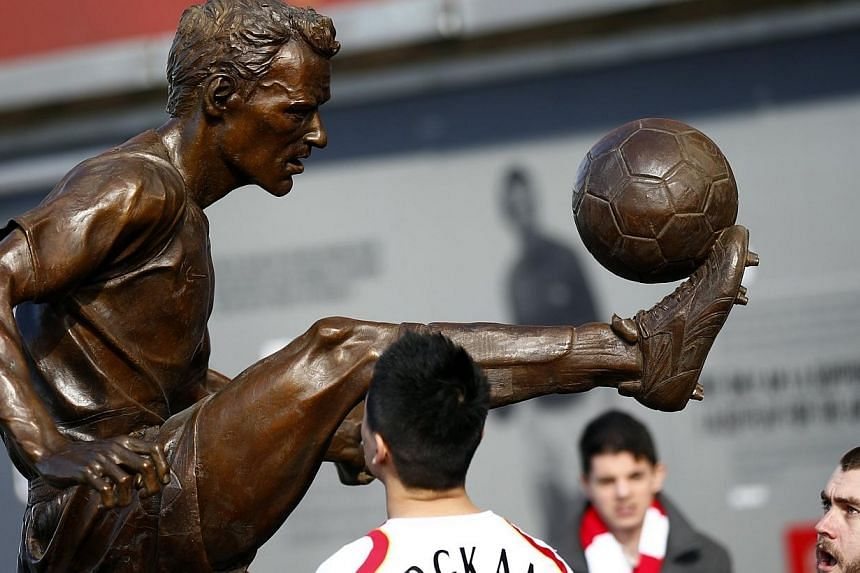 Arsenal fans look at a statue of former striker Dennis Bergkamp after it was unveiled before their English Premier League soccer match against Sunderland at the Emirates Stadium in London, Feb 22, 2014. -- PHOTO: REUTERS