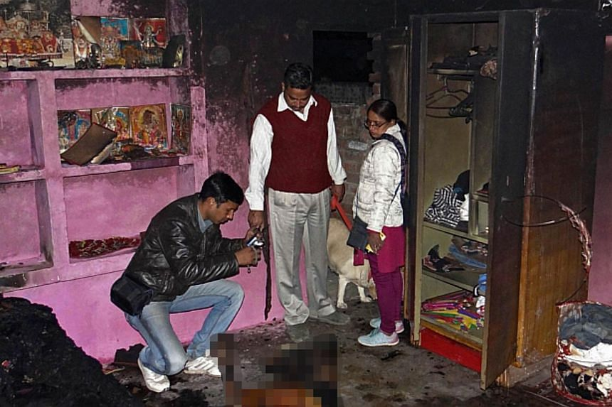 In this photograph taken on Feb 20, 2014, investigators take photographs at the charred residence where accused Indian auto-rickshaw driver Bunty Sharma immolated himself after killing his wife, US national Arian Willingar from Pennsylvania, in Agra.