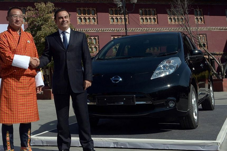 Nissan Motor Corporation chief executive officer Carlos Ghosn (right) and Bhutanese Prime Minister Tshering Tobgay shake hands after unveiling the Nissan Leaf electric vehicle in Thimphu on Feb 21, 2014.It was the world's last hold-out against
