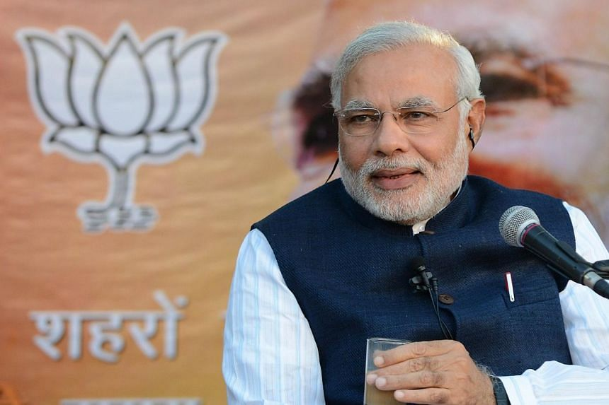Chief Minister of India's western Gujarat state and Bharatiya Janata Party (BJP) prime ministerial candidate Narendra Modi, seen holding a cup of tea, takes part in the 'talk over tea' broadcast and election campaign in Ahmedabad on Feb 12, 2014.&nbs
