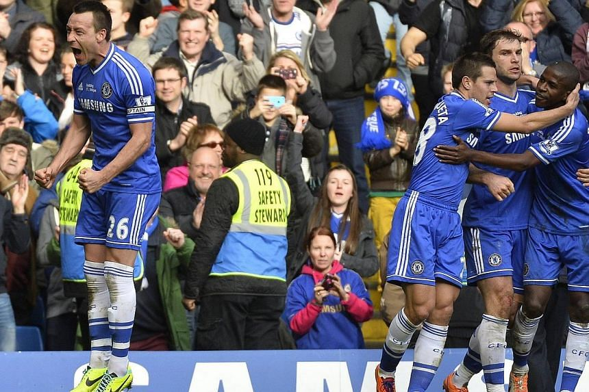 Chelsea's John Terry (left) and team mates celebrate after Everton's Tim Howard scored an own goal during their English Premier League soccer match at Stamford Bridge in London, on Saturday, Feb 22, 2014.Captain John Terry grabbed a stoppage-ti