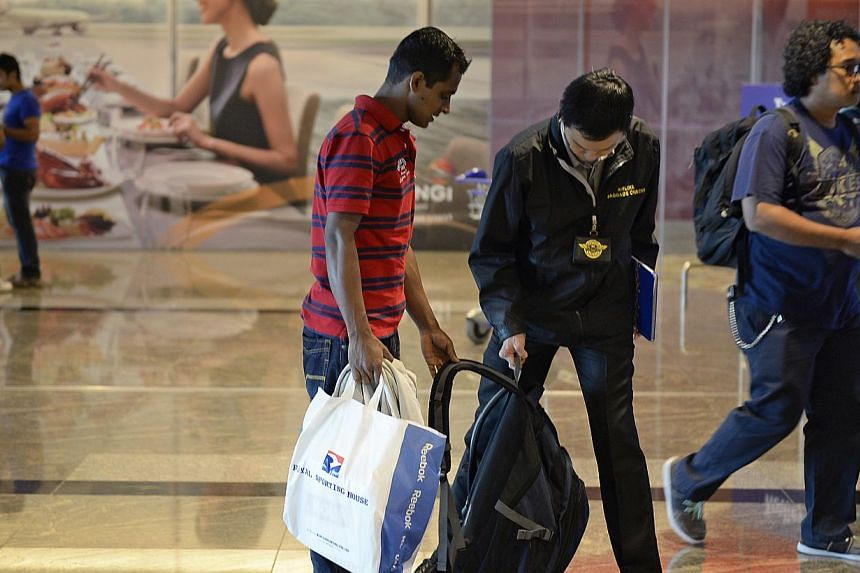 Baggage checkers are stationed at the glass doors leading to the departure lounge. Passengers whose bags are too heavy are sent to check in the bags.