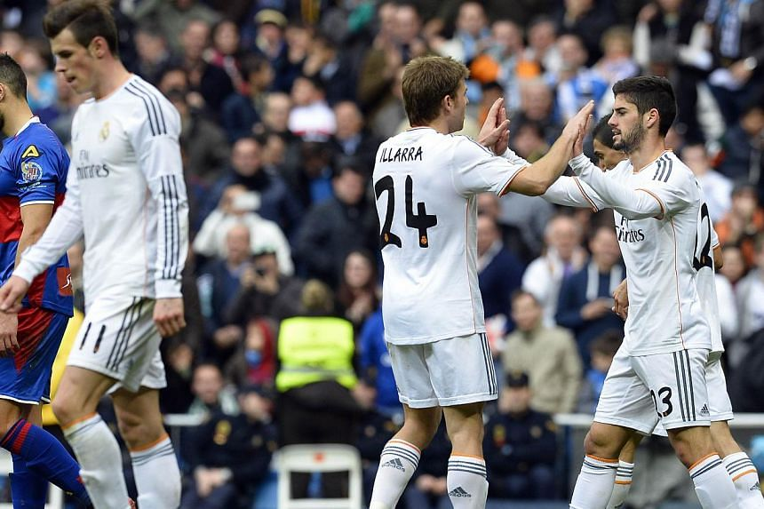 Real Madrid's midfielder Isco (right) is congratuled after scoring by Real Madrid's midfielder Asier Illarramendi (centre) as Real Madrid's Welsh striker Gareth Bale (left) walks during their Spanish league football match against Elche at the Santiag