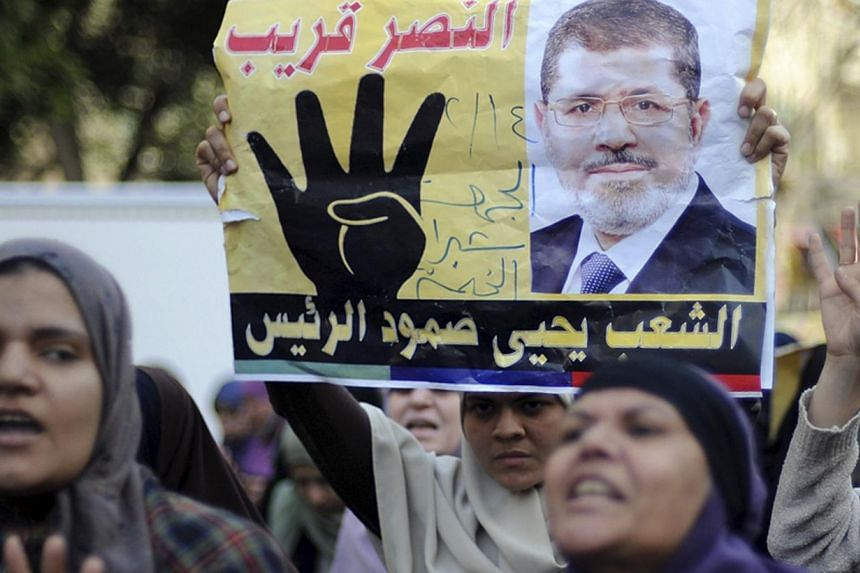 """Supporters of Muslim Brotherhood and ousted Egyptian President Mohamed Mursi shout slogans against the military and the interior ministry as they gesture with the sign """"Rabaa"""", or """"Four"""", during a protest around Ain Shams square in east Cairo Feb 14,"""