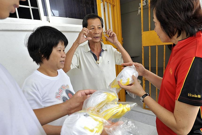 Ms Chua An Na, 68 receiving some masks from MP Lee Bee Wah, whilst her husband simulates putting on the mask. MsLee is also the Grassroot Advisor to Nee Soon South GRO. -- ST PHOTO: MATTHIAS HO