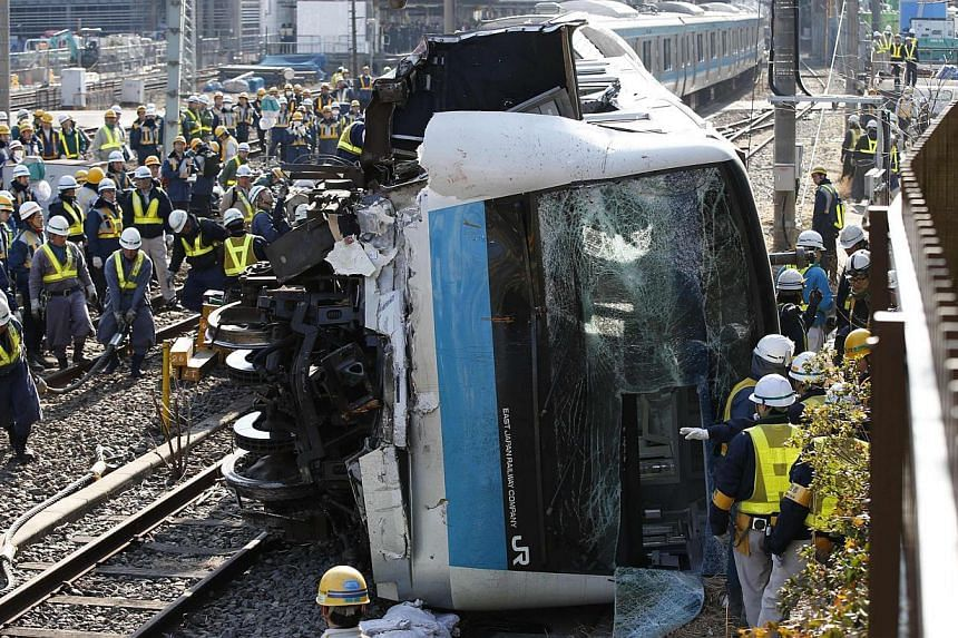 Officials inspect a train after it collided with a maintenance car near Kawasaki Station in Kawasaki, south of Tokyo on Feb 23, 2014. An empty commuter train jumped the track near Tokyo early Sunday, slightly injuring its driver and conductor, railwa