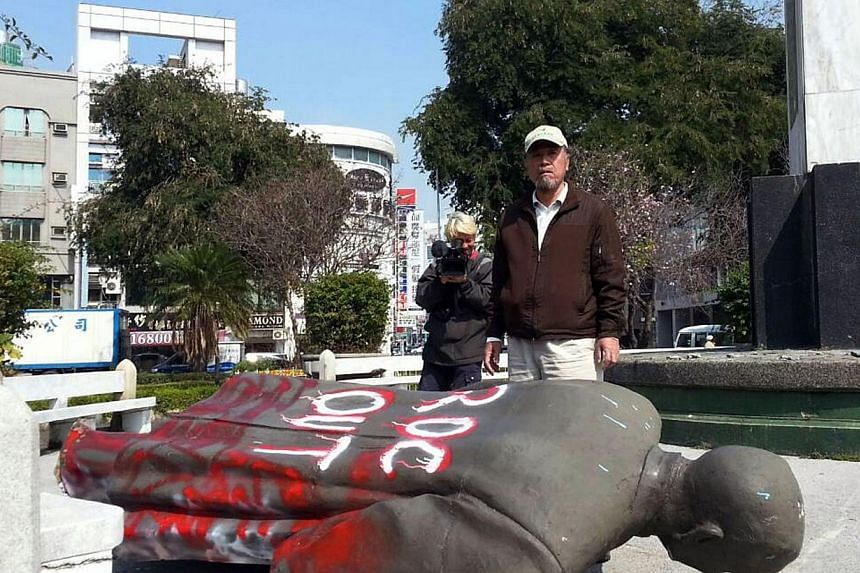 This handout photo taken and received by the Alliance of Referendum for Taiwan on Feb 22, 2014, shows Tsai Ding-gui, chairman of the Alliance of Referendum for Taiwan, standing behind a bronze statue of Sun Yat-sen that was pulled down by dozens of a