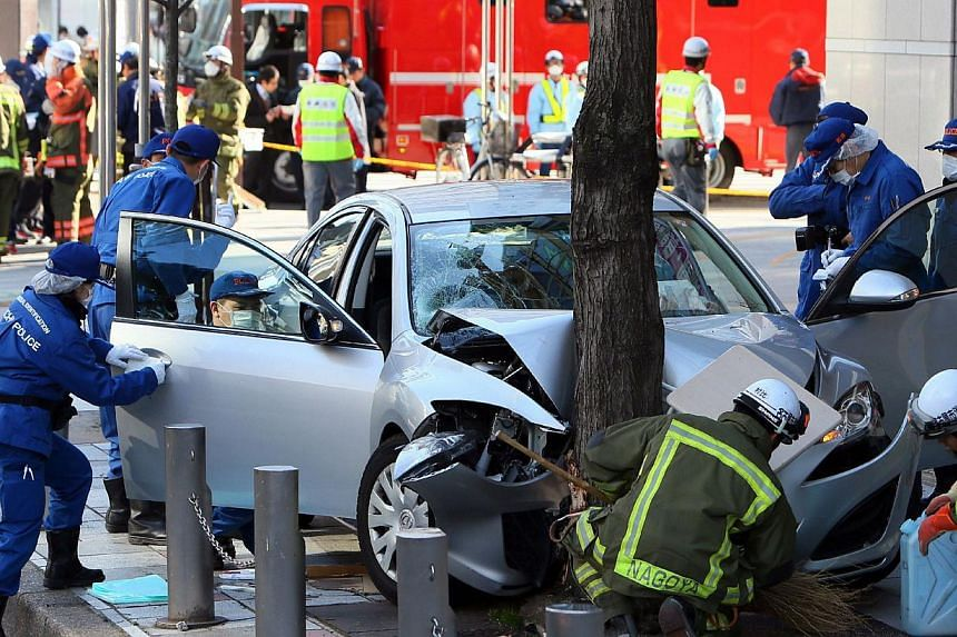 Police investigators inspect a vehicle after it crashed onto a pavement and hit 12 pedestrians in Nagoya in Aichi prefecture, central Japan on Feb 23, 2014.-- PHOTO: AFP