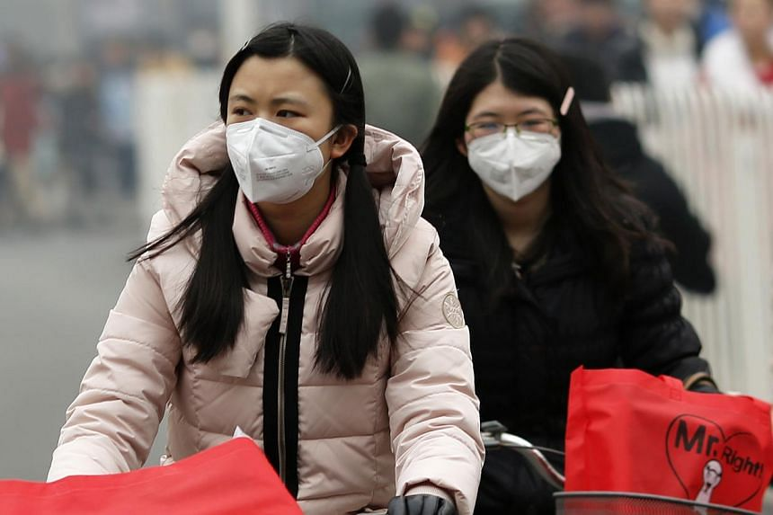 Girls wearing masks ride bicycles amid the heavy haze in Beijing on Feb 22, 2014. -- PHOTO: REUTERS