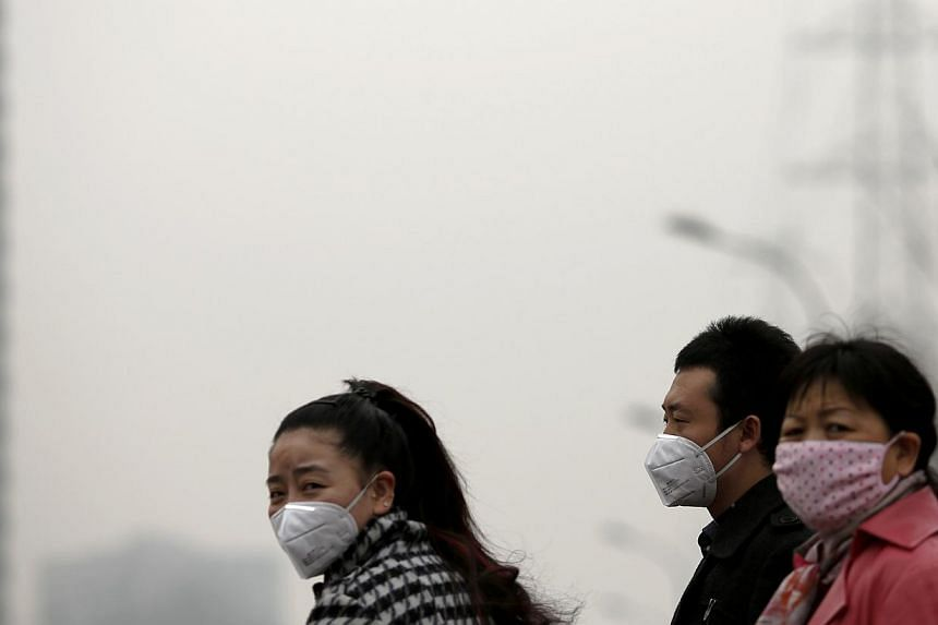 People wearing masks wait for a taxi amid the heavy haze in Beijing on Feb 22, 2014. -- PHOTO: REUTERS