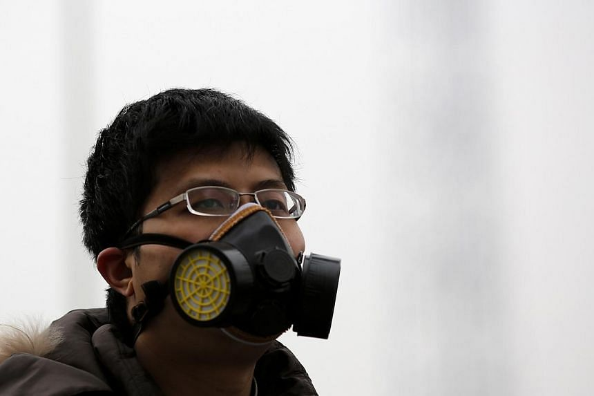 A man wearing a mask makes his way amid the heavy haze in Beijing on Feb 22, 2014. -- PHOTO: REUTERS