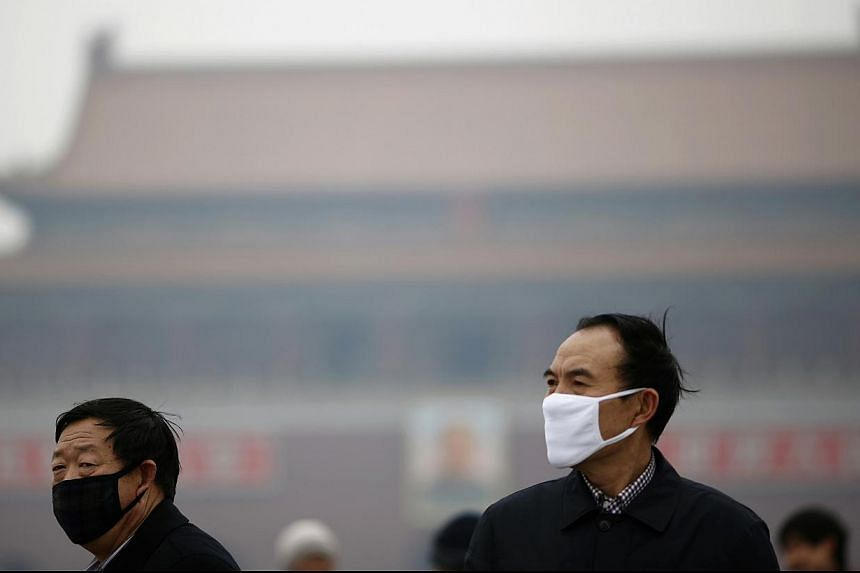 People wearing masks are seen on a hazy day at Tiananmen Square in Beijing on Feb 13, 2014. -- FILE PHOTO: REUTERS