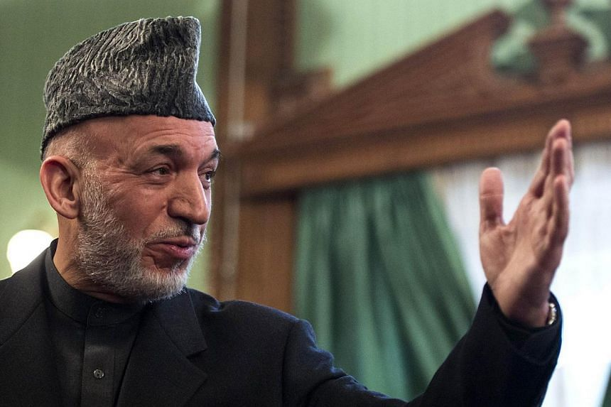 Afghan President Hamid Karzai gestures during a press conference at the Presidential Palace in Kabul on Jan 25, 2014.Karzaipostponed on Sunday a planned visit to Sri Lanka over the killing of 19 Afghan soldiers in an assault by Taleban mi