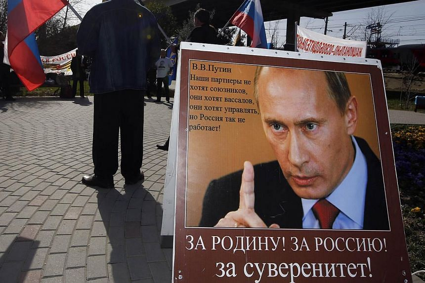 """A poster of Russian Vladimir Putin reading """" For Motherland, for Russia, for Sovereignty"""" is seen during a pro-government demonstration in Sochi at the 2014 Sochi Winter Olympics, Feb 23, 2014.Smoothly run and sometimes dazzling, the Sochi Olym"""