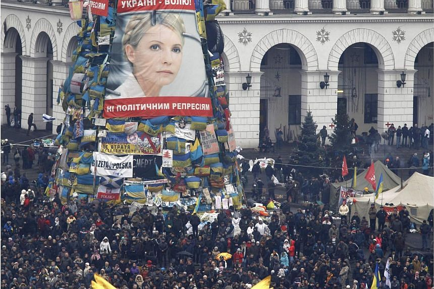 Anti-government protesters stand front of a poster showing jailed Ukrainian opposition leader Yulia Tymoshenko in the Independence Square in Kiev on Feb 22, 2014. -- PHOTO: REUTERS