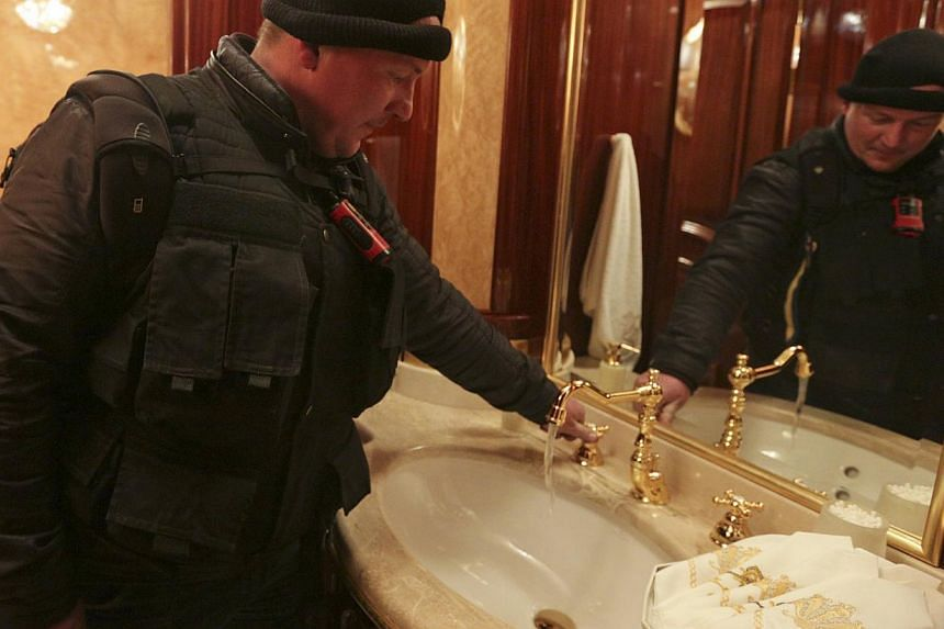 A man turns on a water tap inside the residence as anti-government protesters and journalists walk on the grounds of the Mezhyhirya residence of Ukraine's President Viktor Yanukovich in the village Novi Petrivtsi outside Kiev on Feb 22, 2014. -- PHOT