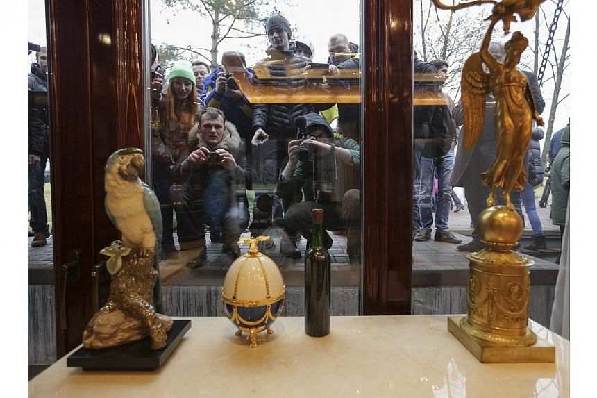 People look through windows of the Mezhyhirya residence of Ukraine's President Viktor Yanukovich as anti-government protesters and journalists walk on the grounds in the village Novi Petrivtsi, outside Kiev on Feb 22, 2014. -- PHOTO: REUTERS