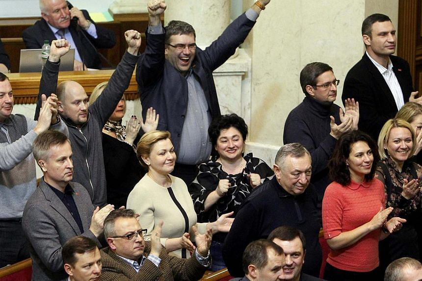 Opposition members, including leader Vitaly Klitschko (Top R) celebrate as the Ukraine's Parliament voted to remove President Viktor Yanukovich from office hours after he abandoned his Kiev office to protesters during a session in Kiev on Feb 22, 201