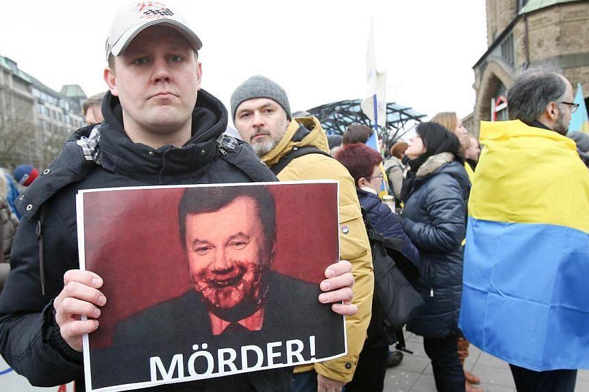 "A demonstrator holds a portrait of Ukrainian President Viktor Yanukovych reading ""Murderer!"" during a demonstration in support of the Ukrainian opposition on February 22, 2014 in Hamburg, northern Germany. -- PHOTO: AFP"