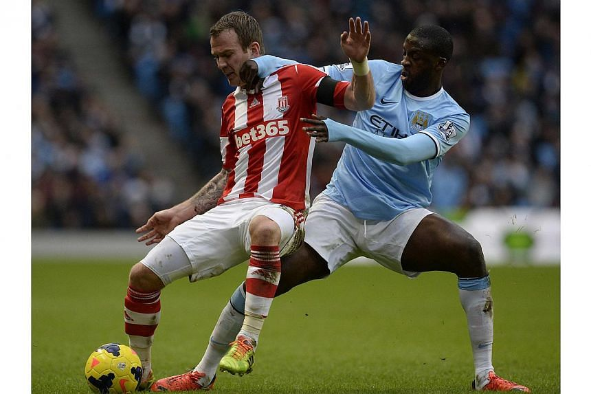 Manchester City's Yaya Toure (right) challenging Stoke City's Glenn Whelan during their English Premier League match at the Etihad Stadium in Manchester, on Feb 22, 2014. Toure scored the only goal as Manchester City stayed in touch at the top