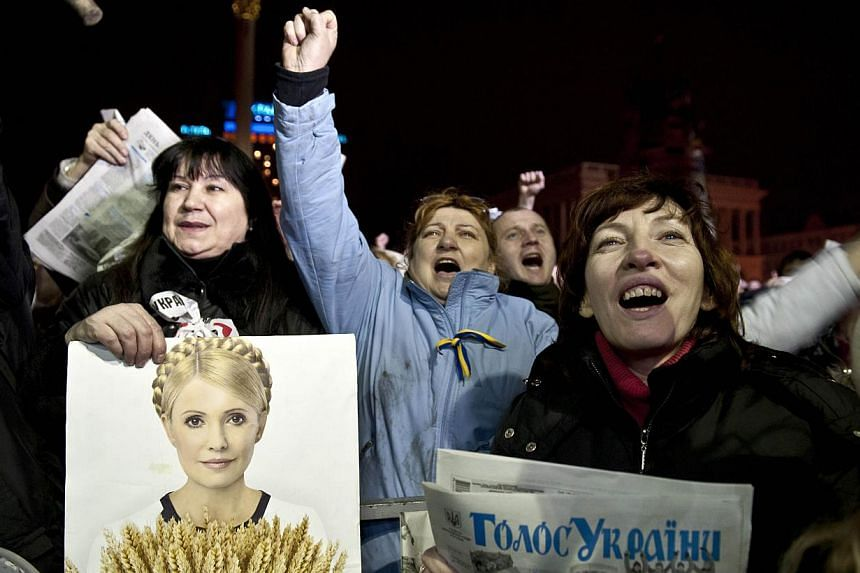 """An opposition protester holds a picture of newly freed Ukrainian opposition icon Yulia Tymoshenko as she delivers a speech during a rally at Independence Square in Kiev on Feb 22, 2014. """"Yulia, Yulia!"""" the crowd chanted on Saturday, Feb 22, 2014,"""