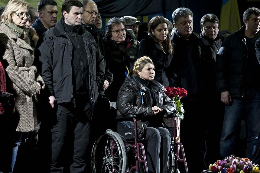 Newly freed Ukrainian opposition icon and former prime minister Yulia Tymoshenko (centre) in wheelchair, attends a rally on Kiev's Independance square on Feb 22, 2014, after her release.France on Sunday welcomed the surprise release from prison