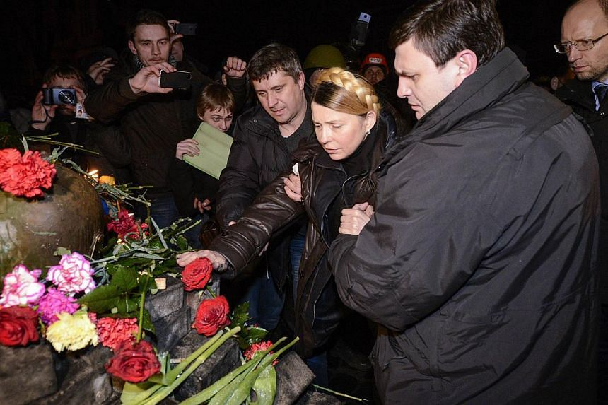Newly freed Ukrainian opposition icon Yulia Tymoshenko visits the site where an opposition protester was killed near a barricade on Grushevsky street in Kiev on Feb 22, 2014. -- PHOTO: AFP