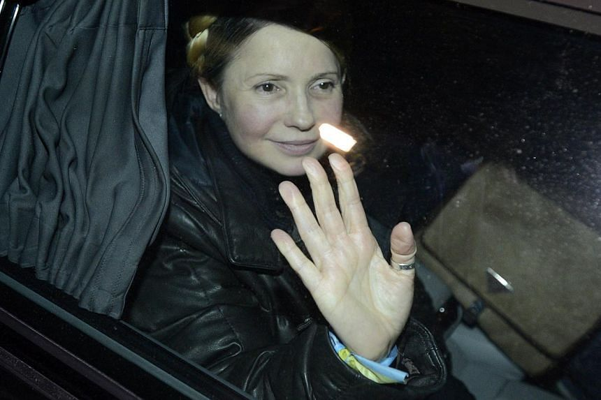 Newly freed Ukrainian opposition icon Yulia Tymoshenko waves from a car after arriving in Kiev on Feb 22, 2014. -- PHOTO: AFP