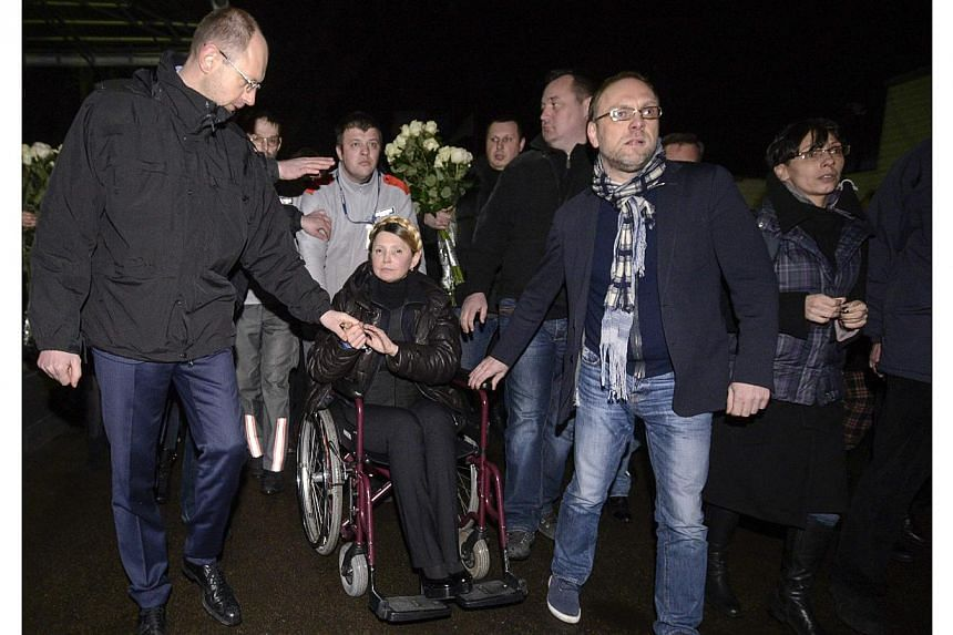 Ukrainian opposition leader Yulia Tymoshenko (centre) holds her associate Arseny Yatsenyuk's hand (left) as she is transported on a wheelchair upon her arrival at the airport in Kiev on Feb 22, 2014. -- PHOTO: REUTERS