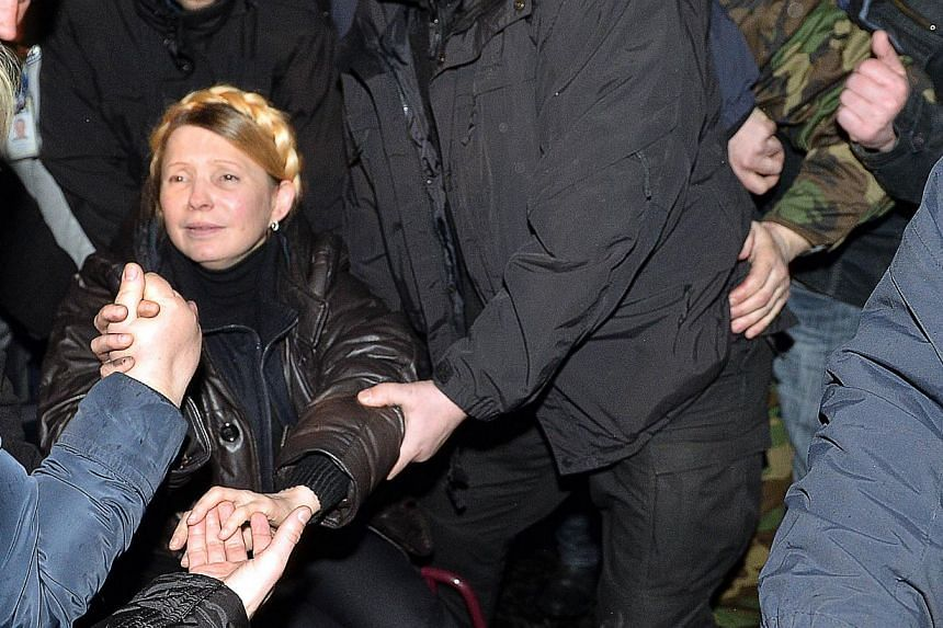 People greet newly freed Ukrainian opposition icon Yulia Tymoshenko as she arrives to speak at Independence Square on Feb 22, 2014, moments after parliament voted to hold early presidential elections in May. -- PHOTO: AFP