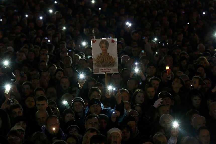 Anti-government protesters hold a poster of Ukrainian opposition leader Yulia Tymoshenko as they await for her arrival in Independence Square in Kiev on Feb 22, 2014. -- PHOTO: AFP