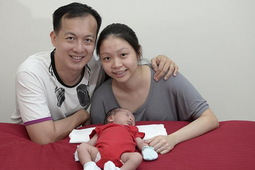 Dr Teoh Ren Shang and his wife Victoria with their son Xavier, who was born in the master bedroom of their HDB flat. -- ST PHOTO: MUGILAN RAJASEGERAN