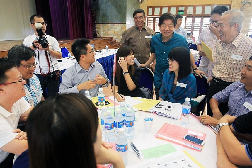 National Development Minister Khaw Boon Wan (standing, in blue shirt) chatting to grassroots leaders at the post-Budget dialogue at Fuchun Community Club yesterday. -- PHOTO: LIANHE ZAOBAO