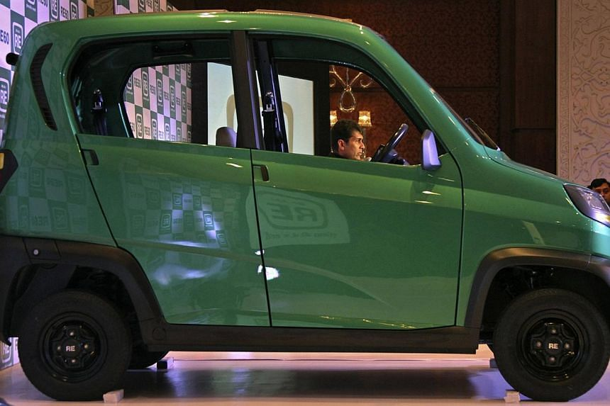 Bajaj's Managing Director Rajiv Bajaj is seen through the windows of the newly launched four-wheeled RE60 in New Delhi in this Jan 3, 2012 file photo. -- FILE PHOTO: REUTERS