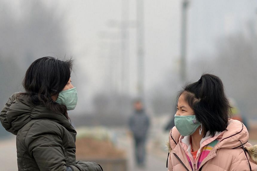 This picture taken on Feb 23, 2014 shows residents wearing masks and talking to each other on a street in smog-covered Beijing. Dangerous smog which has blighted swathes of northern China in recent days has prompted a spike in air purifier sales, loc