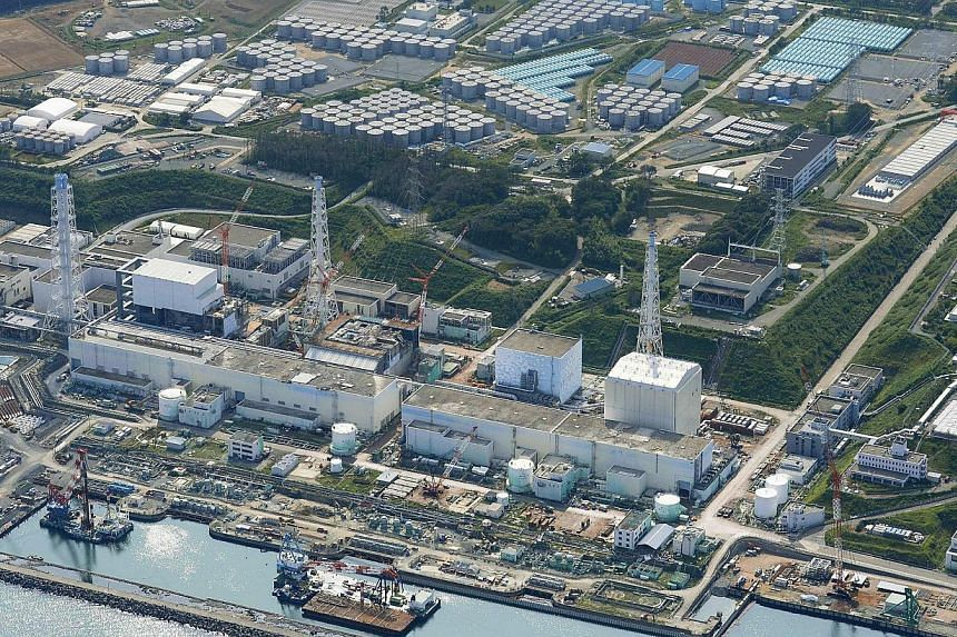 An aerial view shows the Tokyo Electric Power Co.'s (TEPCO) tsunami-crippled Fukushima Daiichi nuclear power plant and its contaminated water storage tanks (top) in Fukushima, in this photo taken by Kyodo on Aug 31, 2013. -- FILE PHOTO: REUTERS