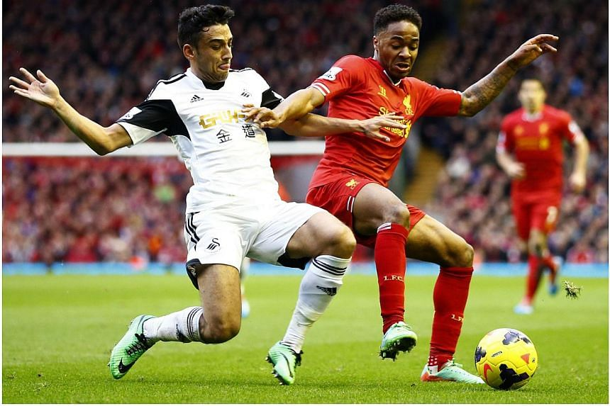 Liverpool's Raheem Sterling (right) challenges Swansea's Neil Taylor during their English Premier League soccer match at Anfield in Liverpool, northern England, on Feb 23, 2014. -- PHOTO: REUTERS