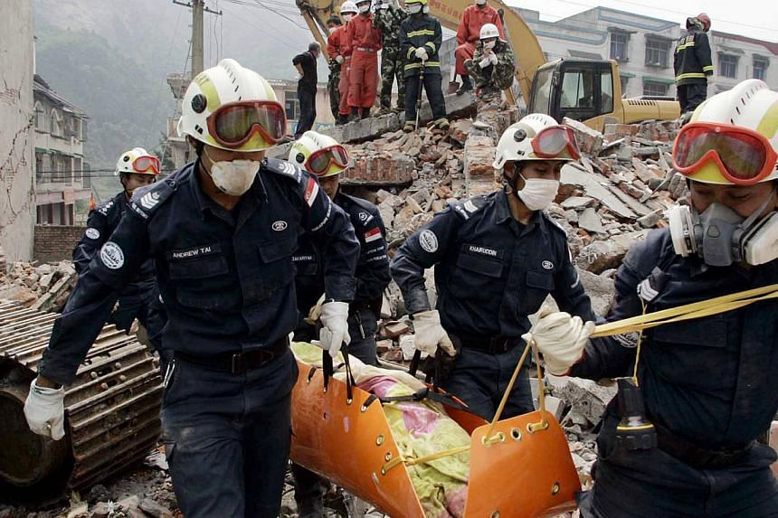 In this file picture dated Nov19, 2013, rescuers from the Singapore Civil Defence Force recover the body of Madam Zhong Xianshu, 43, from the debris of a collapsed five-storey building in the worst hit earthquake of Sichuan province in China. -