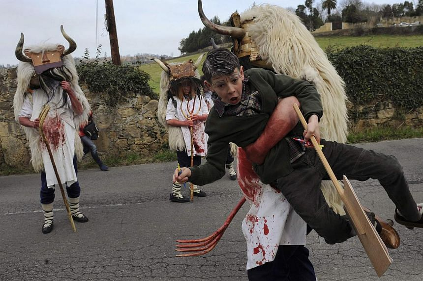 A member of a folk group grabs a child during a parade, part of the VII Xornaes de Mazcares d'Inviernu (VII Winter Mask Meetings) in Valdesoto, near Oviedo, Feb 23, 2014. Groups from different regions of Spain and Portugal attended the gathering and