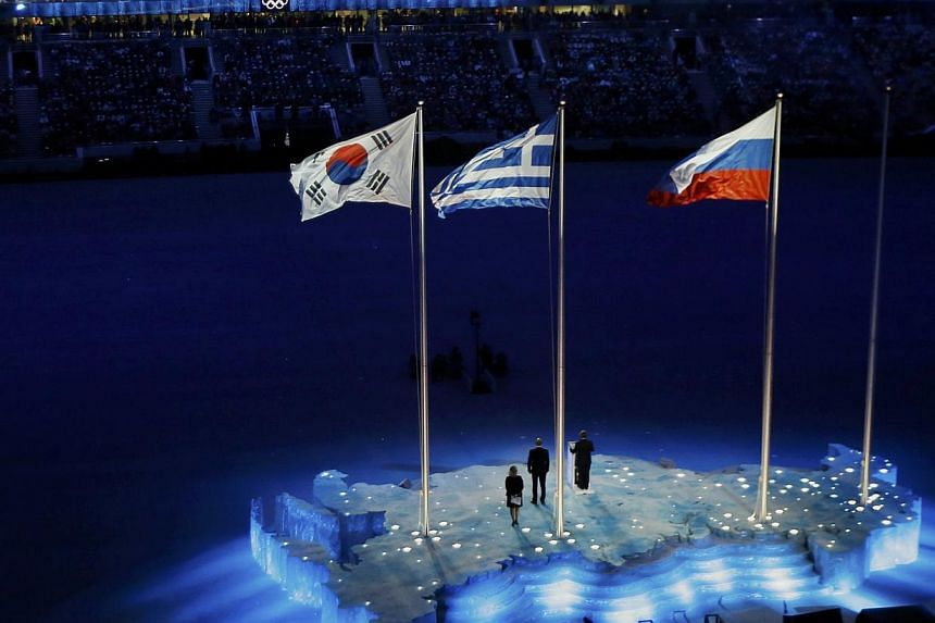 The South Korean, Russian and Greek (from left) national flags are seen raised during the closing ceremony for the 2014 Sochi Winter Olympics, on Feb 23, 2014. -- PHOTO: REUTERS