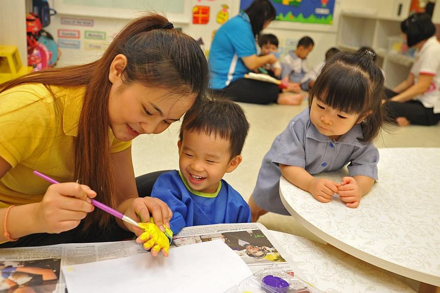 Childcare teacher Yang Tingting with Brandon Goh, two, and 22-month-old Claris Seow at Sparkletots centre in Punggol on Jan 2, 2014. Waiting lists have not shortened at more than half of the childcare centres in Punggol - an area of high demand for c
