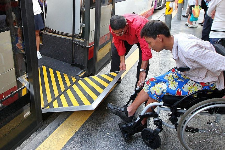 SMRT bus driver Machap Simakarupm helping Mr Patrick Ang to board the bus at a bus stop in the Bugis area. Four more SMRT bus services will be accessible to wheelchair users from Mar 2. -- TNP FILE PHOTO: JONATHAN CHOO