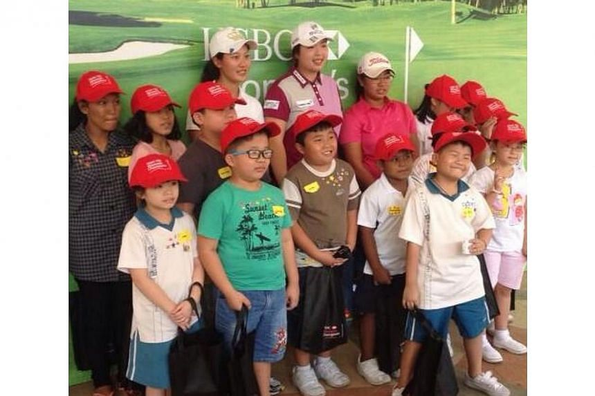 Top China female golfer Feng Shanshan (back row, fourth from left) met with some 24 underprivileged children at Kaki Bukit Community Centre pavilion on Monday, Feb 24, 2014.-- ST PHOTO: CHUA SIANG YEE