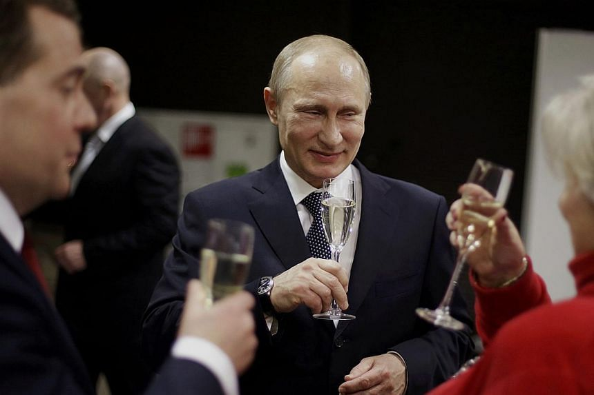 Russian President Vladimir Putin toasts Russian Prime Minister Dmitry Medvedev (left) and figure skating coach Tatiana Tarasova (right) with glasses of champagne in the presidential lounge before the 2014 Winter Olympics closing ceremony in Sochi, Fe