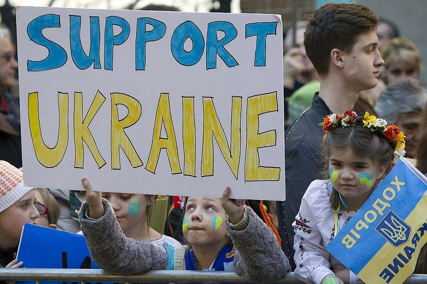 Children hold up signs during a protest across the street from the Ukraine Consulate in the Manhattan borough of New York, Feb 23, 2014.Ukraine said on Monday, Feb 24, 2014, it will need US$35 billion (S$44 billion) in urgent foreign assistance