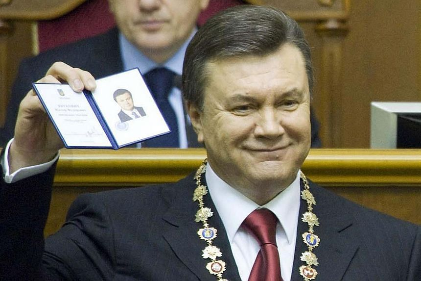 A photo taken on Feb 25, 2010, shows Ukraine's President Viktor Yanukovych holding the presidential certificate after he took oath in the parliament in Kiev.Ukraine issued an arrest warrant for ousted president Viktor Yanukovych on Monday, Feb