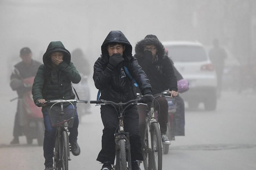 Residents cover their face from dust as they ride their bicycles along a street on a hazy day in Zhengzhou, Henan province on Dec 10, 2013. -- FILE PHOTO: REUTERS