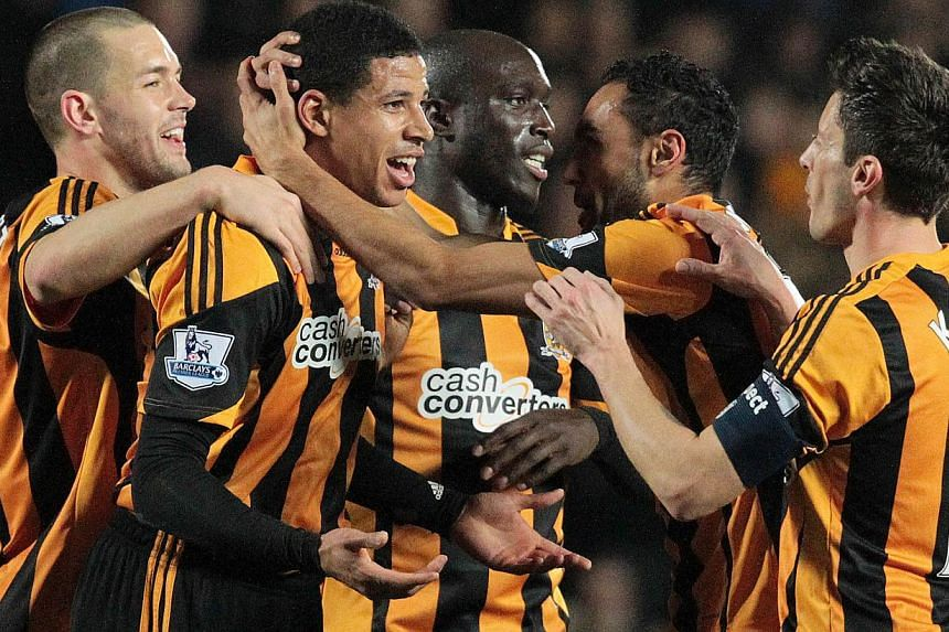 Hull City's English defender Curtis Davies (second, left) celebrates after scoring his team's first goal against Brighton and Hove Albion during an English FA Cup fifth round replay football match between Hull City FC and Brighton and Hove Albion FC
