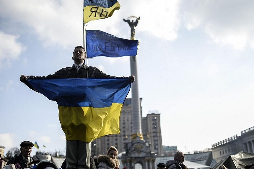 A man holds a Ukrainian flag as he stands on Kiev's Independence Square on Feb 24, 2014.Ukraine's parliament on Tuesday, Feb 25, 2014, put off plans to vote on the formation of a national unity government until Thursday to allow consultations t