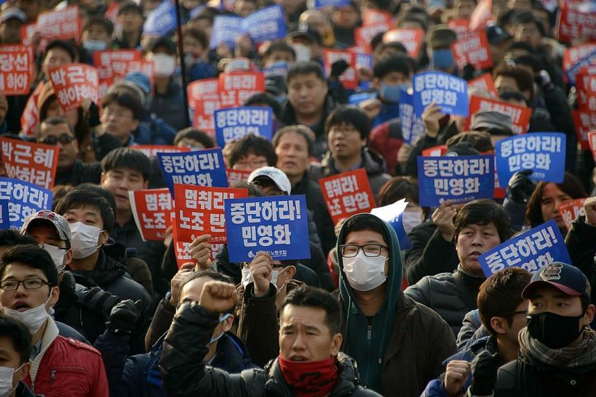 """Anti-government protesters shout slogans and wave banners, some reading: """"stop the crackdown on labour unions"""" as they take part in a rally in Seoul on Feb 25, 2014.South Korean President Park Geun Hye on Tuesday, Feb 25, 2014, unveiled a three"""